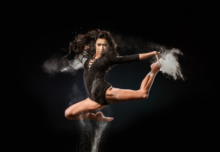 Beautiful ballerina in black bodysuit with talc powder jumping on dark background