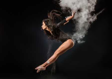 Side view of young ballerina in black bodysuit  with talc powder jumping on dark background Stock Photo