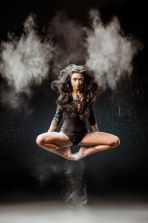 Beautiful ballerina in black bodysuit jumping on dark background with talc powder around Stock Photo