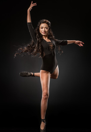 Beautiful ballerina in black bodysuit jumping on dark background with talc powder around Stock Photo