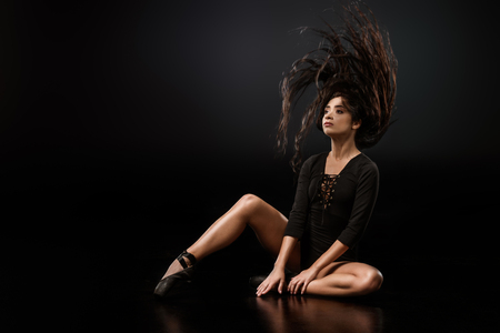 Beautiful ballerina in black bodysuit jumping on dark background with talc powder around 스톡 콘텐츠