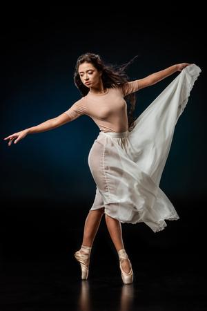 Elegant female ballet dancer in white skirt dancing on dark background