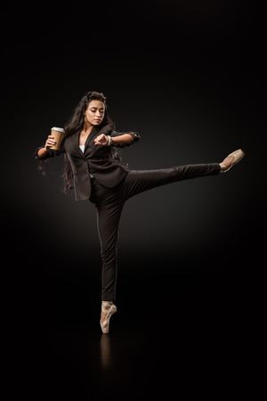 Attractive young businesswoman in formal wear and ballet shoes with coffee to go on black background
