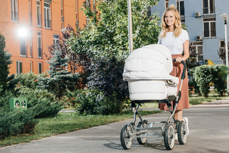 Beautiful blonde mother walking with baby stroller on street