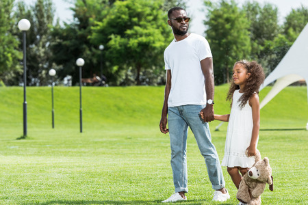 African american father and daughter holding hands and walking in park