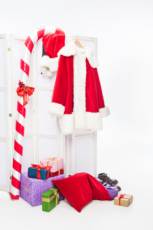 Christmas stick, pile of gift boxes and santa costume on folding screen isolated on white background Stock Photo