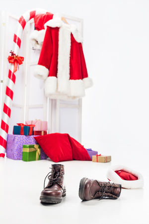 Selective focus of boots and christmas stick, pile of gift boxes and santa costume on folding screen behind isolated on white background