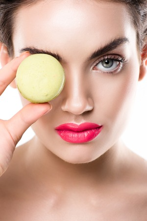 Attractive woman holding green macaroon in front of eye, isolated on white 写真素材