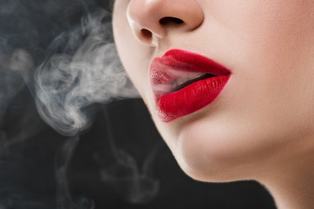 Cropped view of girl with red lips blowing smoke, isolated on grey 免版税图像