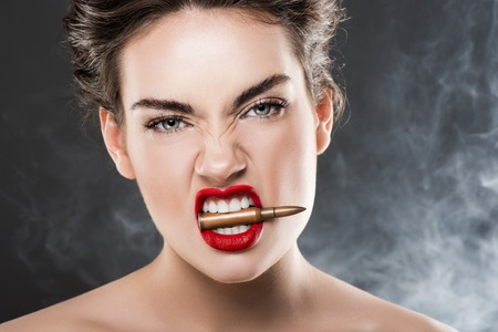 Aggressive woman holding bullet in teeth, on grey with smoke 스톡 콘텐츠
