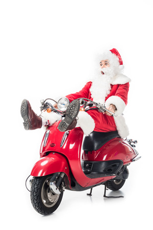 Shocked santa claus in costume riding on scooter isolated on white background