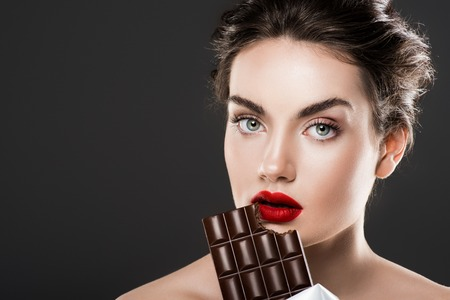 Attractive woman eating chocolate bar, isolated on grey