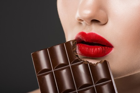 Cropped view of woman with red lips eating chocolate bar, isolated on grey