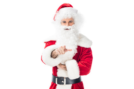 Cheerful santa claus pointing at camera by finger isolated on white background
