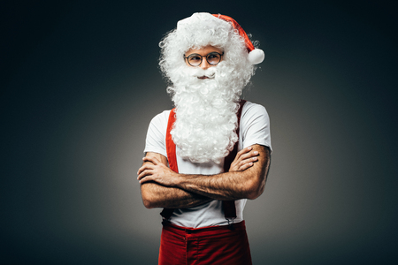 Santa claus in eyeglasses standing with crossed arms isolated on grey background