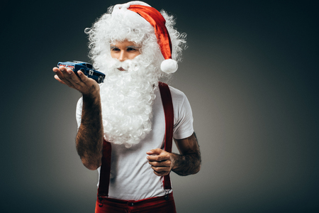 Serious Santa Claus holding toy car on hand palm and standing isolated on grey background