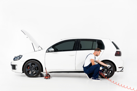 Auto mechanic in blue uniform inflating tire and checking air with gauge pressure on white Reklamní fotografie