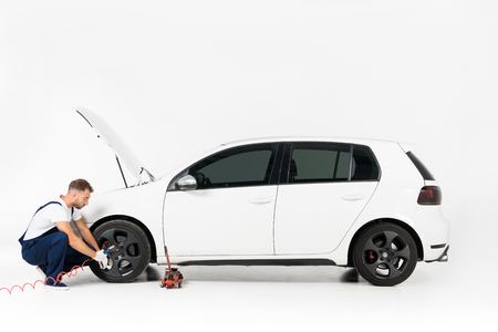 Side view of auto mechanic inflating tire and checking air with gauge pressure on white
