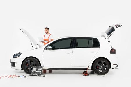 Przystojny mechanik samochodowy korzystający z laptopa w pobliżu samochodu z otwartym kapturem na białym tle