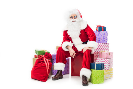 Pensive santa claus sitting on pile of gift boxes isolated on white background Stock Photo