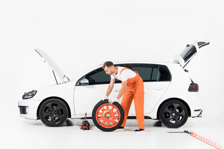 Auto mechanic pushing car tire on white