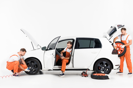 Handsome auto mechanic inflating tire, using laptop and taking tire on white Reklamní fotografie - 110037240
