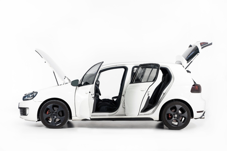 Side view of new white car with open doors and open hood on white