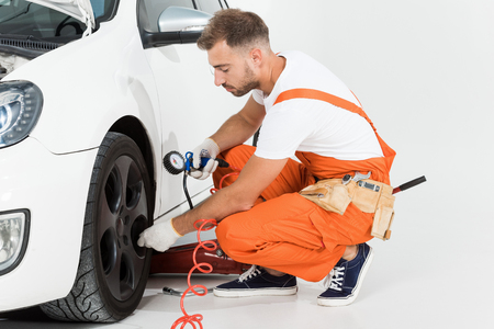 Handsome auto mechanic fixing car tire on white Reklamní fotografie