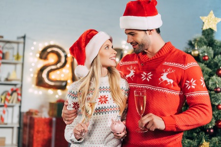 Couple in santa hats with champagne glasses holding piggy bank with savings for christmas Standard-Bild