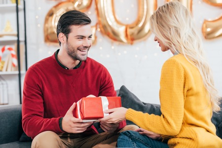 Happy beautiful couple gifting present at home with 2019 golden balloons Stock Photo