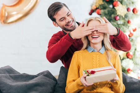 Handsome man closing eyes and making surprise with gift box for woman at home with christmas tree