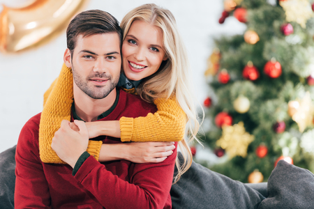 Happy woman embracing her boyfriend at home with christmas tree