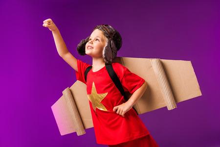 Niño sonriente con alas de avión y gafas de pie con el brazo extendido para volar aislado en púrpura Foto de archivo