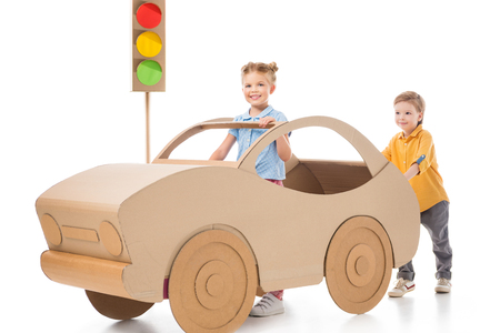 Adorable sister driving cardboard car while brother pushing her, on white and traffic lights on background