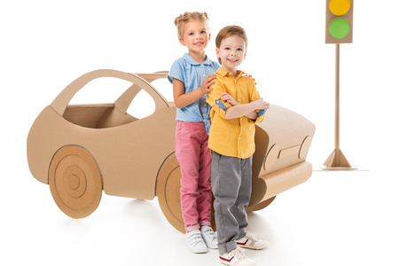 Adorable children posing near cardboard car and traffic lights, on white