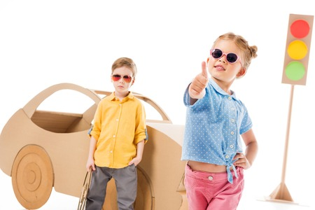 Adorable stylish child in sunglasses showing thumb up while boy standing near cardboard car and traffic lights, on white