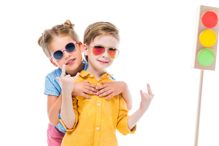 Adorable children in sunglasses, boy showing rock n roll signs, isolated on white with cardboard traffic lights on background Standard-Bild - 110038221