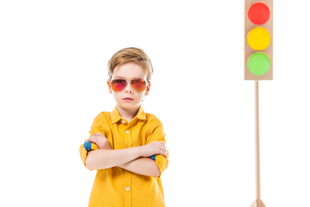Adorable confident boy in sunglasses posing with crossed arms, isolated on white with cardboard traffic lights, isolated on white Stock fotó