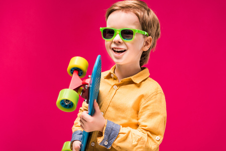 Adorable smiling boy in sunglasses posing with skateboard isolated on red