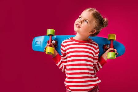 Adorable stylish kid posing with penny board isolated on red Stock Photo