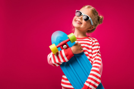 Happy stylish child in sunglasses posing with skateboard isolated on red