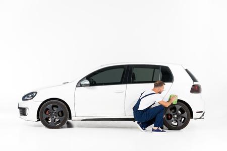 Automechaniker hocken und reinigen Auto nach der Reparatur auf Weiß repair