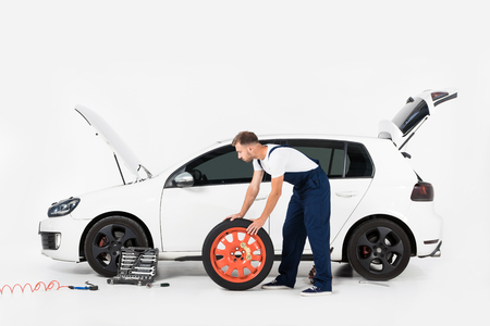 Side view of auto mechanic pushing tire to change old one on white Stock Photo