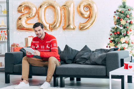 Happy man using digital tablet during 2019 new year 写真素材