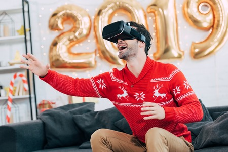 Excited man gesturing and using virtual reality headset during 2019 new year