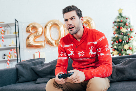 Concentrated man playing video game with joystick during new year 写真素材