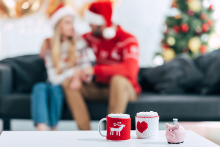 Christmas coffee cups and piggy bank with banknote on table, couple sitting behind Stock Photo
