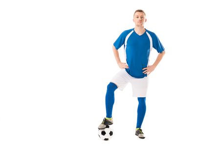Confident young soccer player standing with hands on hips and looking at camera isolated on white