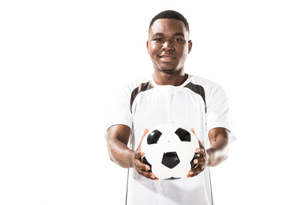 Handsome happy young african american sportsman holding soccer ball and smiling at camera isolated on white