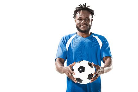 Jugador de fútbol americano africano sosteniendo la pelota y sonriendo a la cámara aislada en blanco